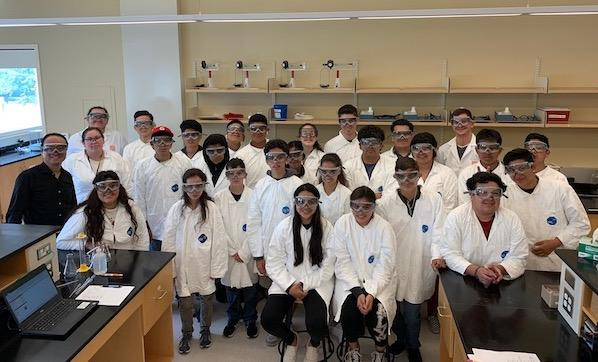 Juntos campers taking group photo in lab coats in lab