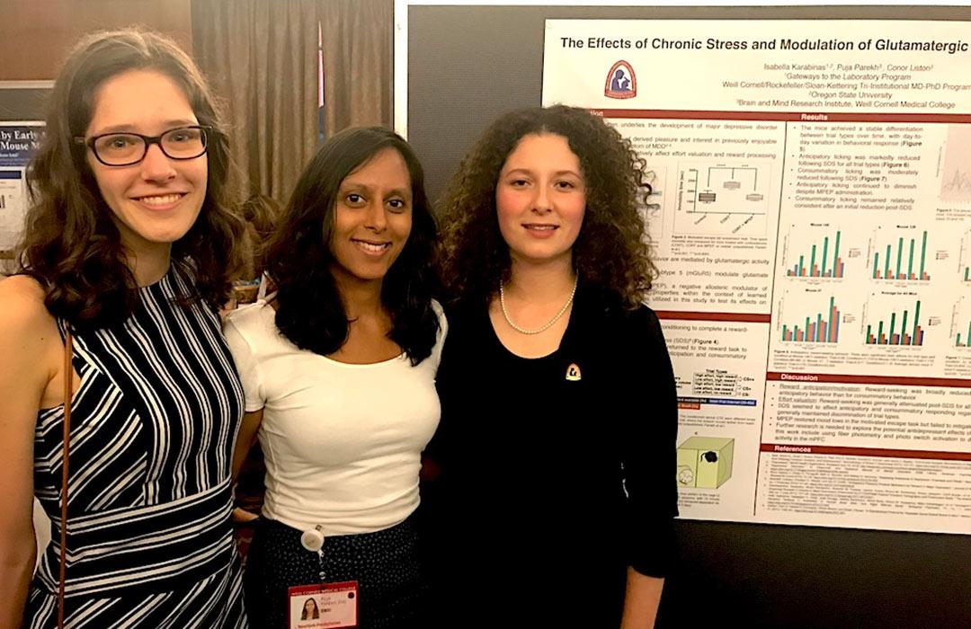 Bella Karabinas with colleagues in front of research poster
