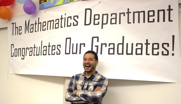 Micheal Lopez smiling under Math Graduate sign