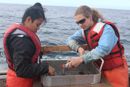 Sarah Henkel with colleague checking out samples in a boat