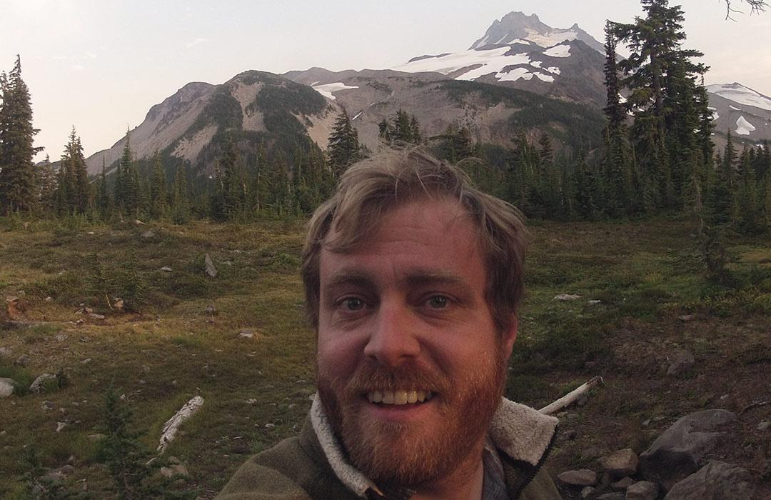 Ken Walsh taking a selfie with Mount Jefferson behind him