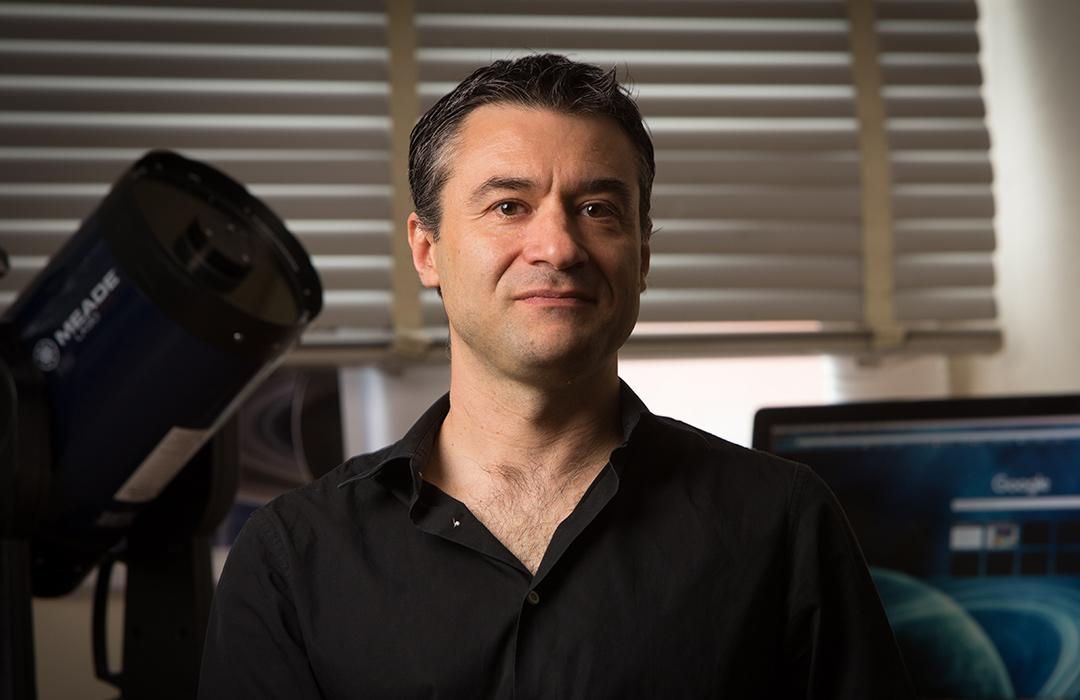 Davide Lazzati sitting in office space with equipment
