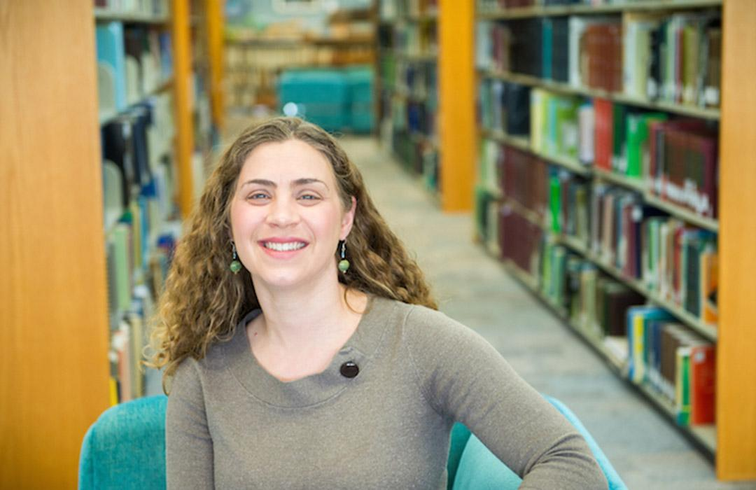 Sarah Henkel sitting in front of book shelves