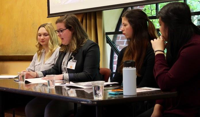 female students sitting on panel during meeting