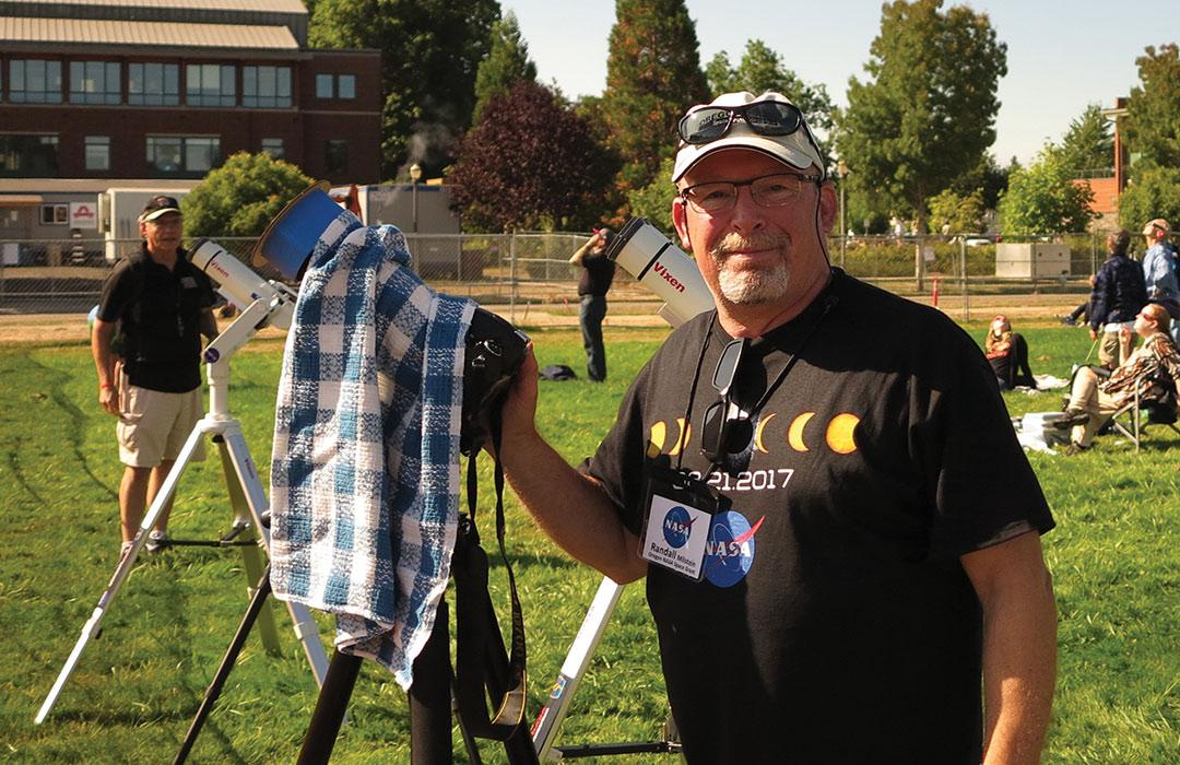 Randall Milstein working microscope in field with viewers of Solar Eclipse