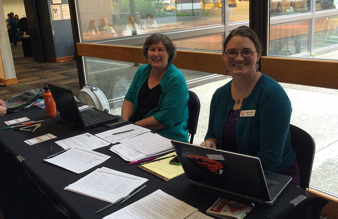 Margie Haal with colleague and sign-in table in La Sells