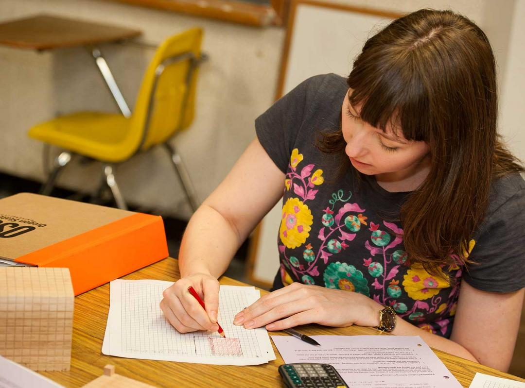 female student working on math on table