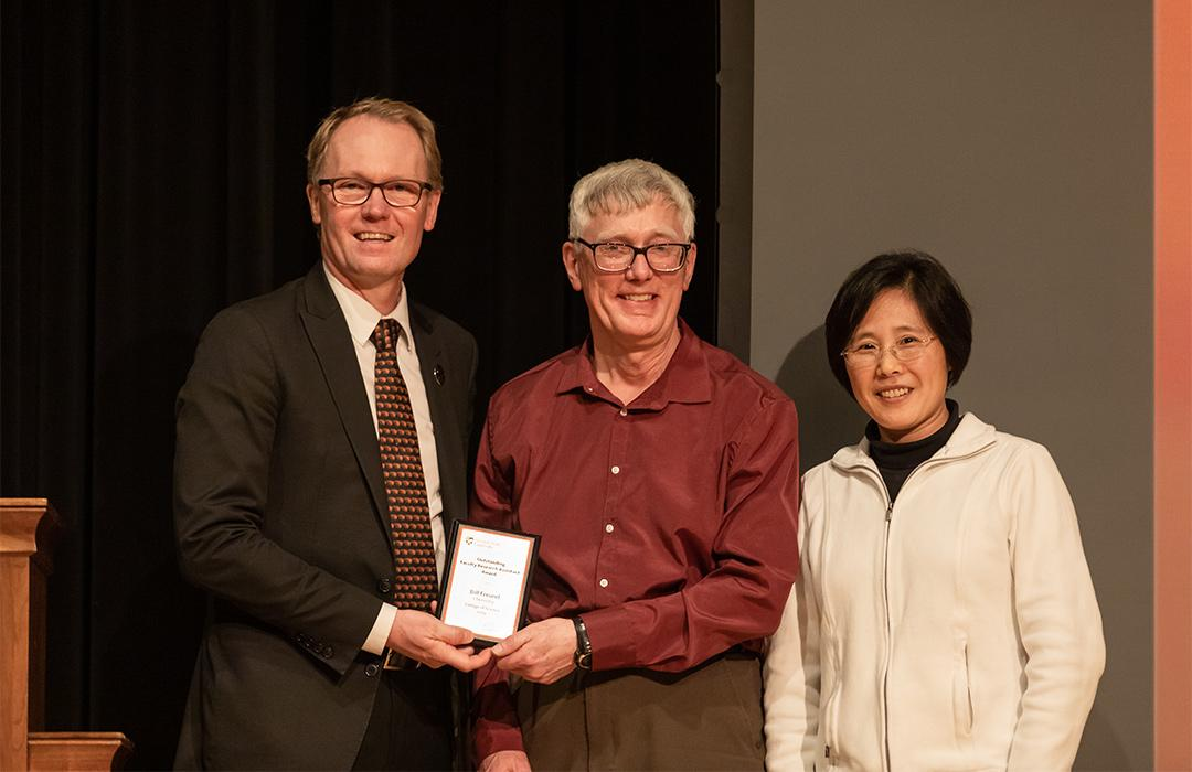 Bill Freund receiving award from colleagues on stage