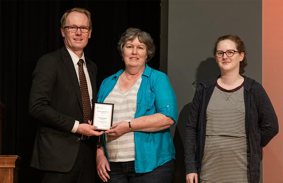 Margie Haak receiving award from faulty on stage