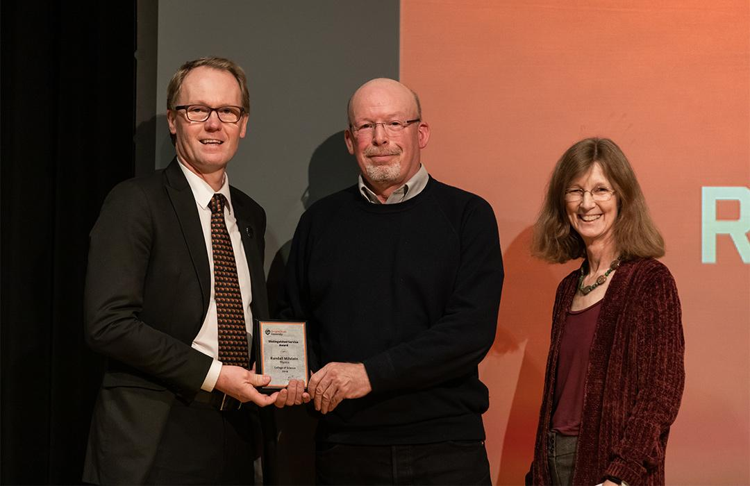 Randall Milstein receiving award from colleagues on stage