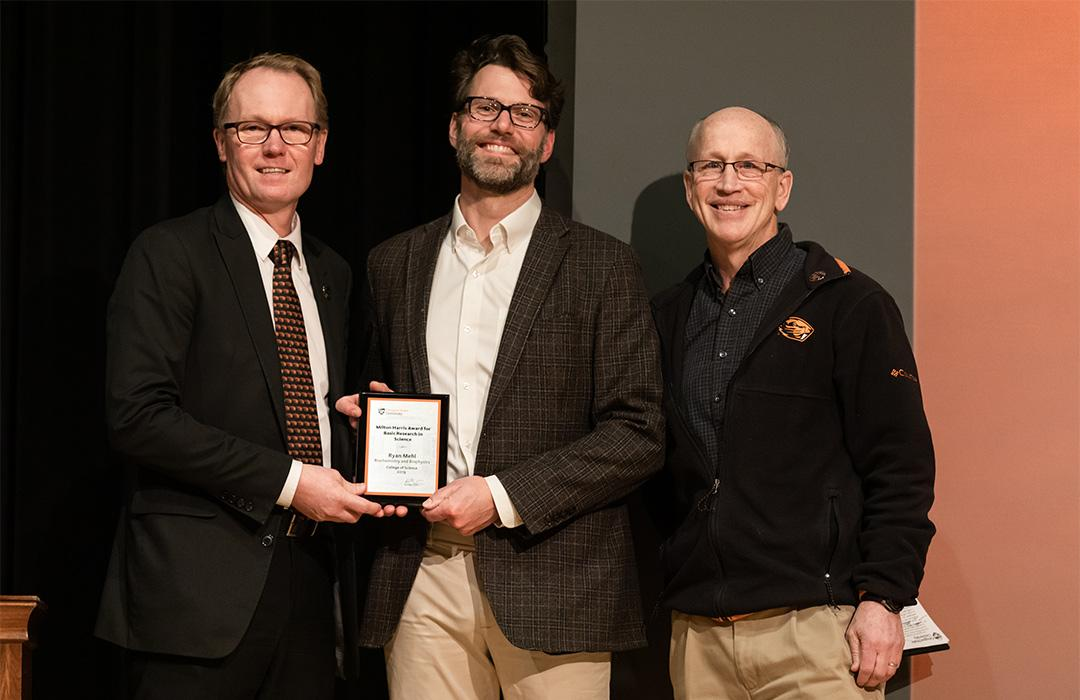 Ryan Mehl receiving award on stage with colleagues
