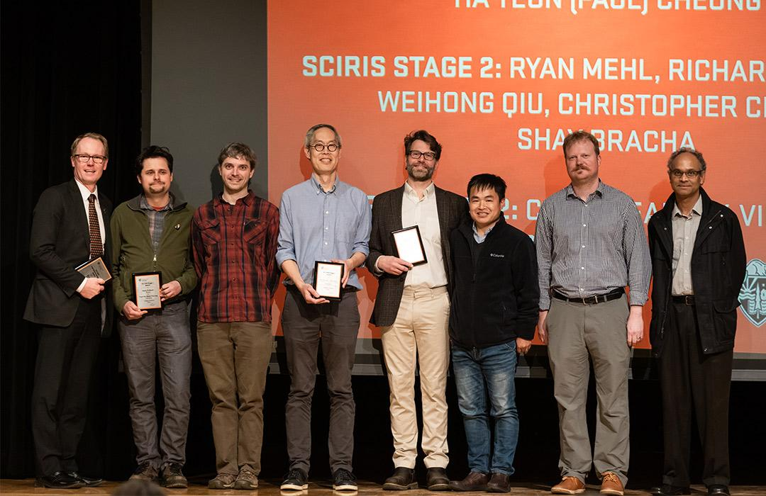 award recipients holding up awards on stage with colleagues