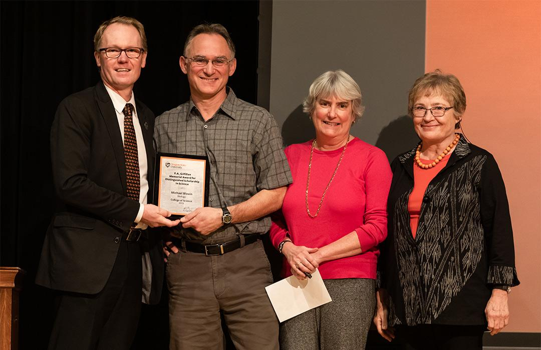 Michael Blouin receiving award from colleagues on stage