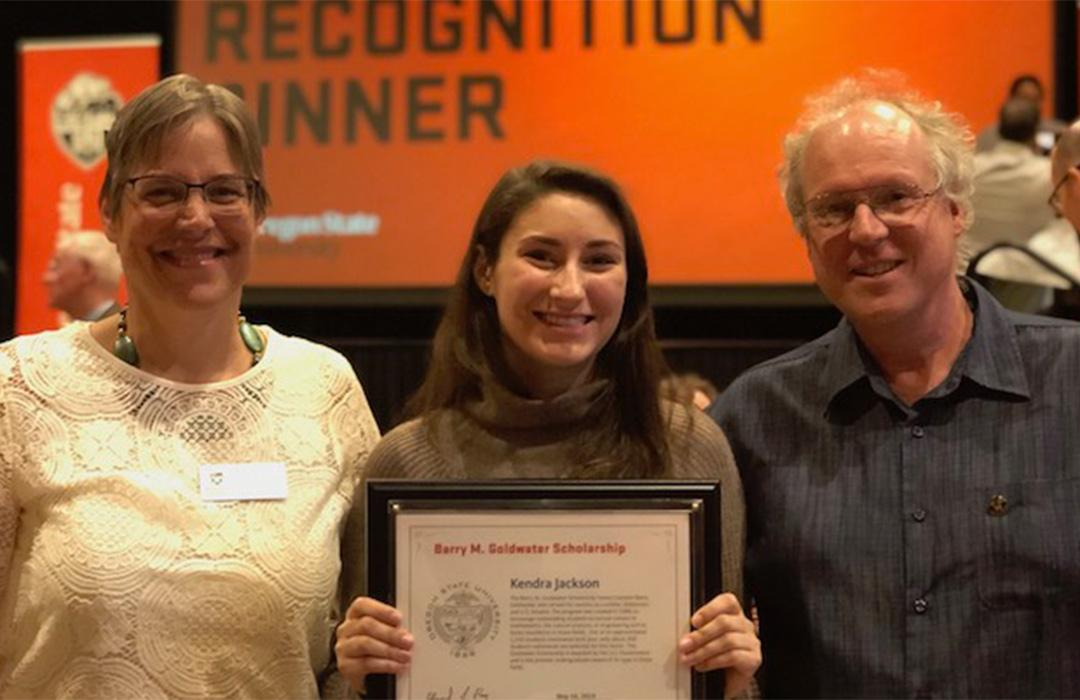 Kendra holding award with Kari Van Zee and Michael Freitag in auditorium
