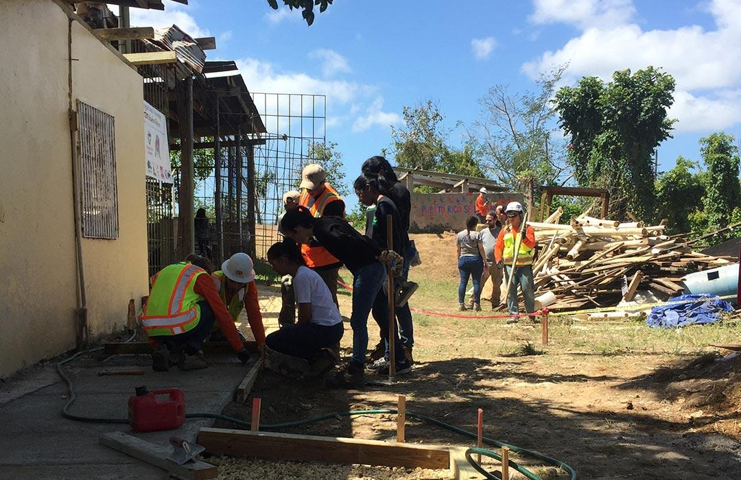 group of people fixing up hurricane-damaged building
