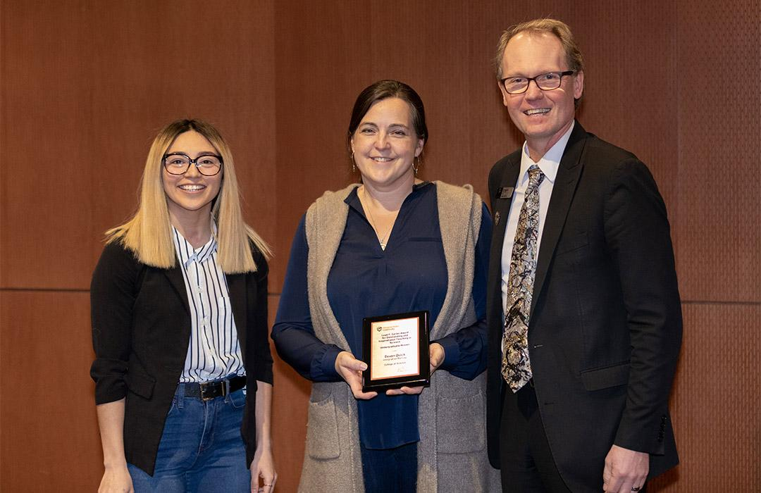 Devon Quick poses with award with microbiology student Arisa Larmay (left) and Dean Haggerty (right)