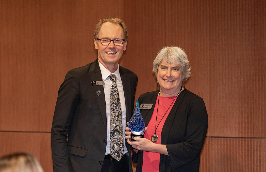 Virginia Wes receiving an award from Dean Haggerty
