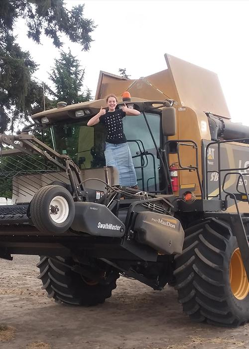 """Girl giving the """"thumbs up"""" on top of a big combine"""