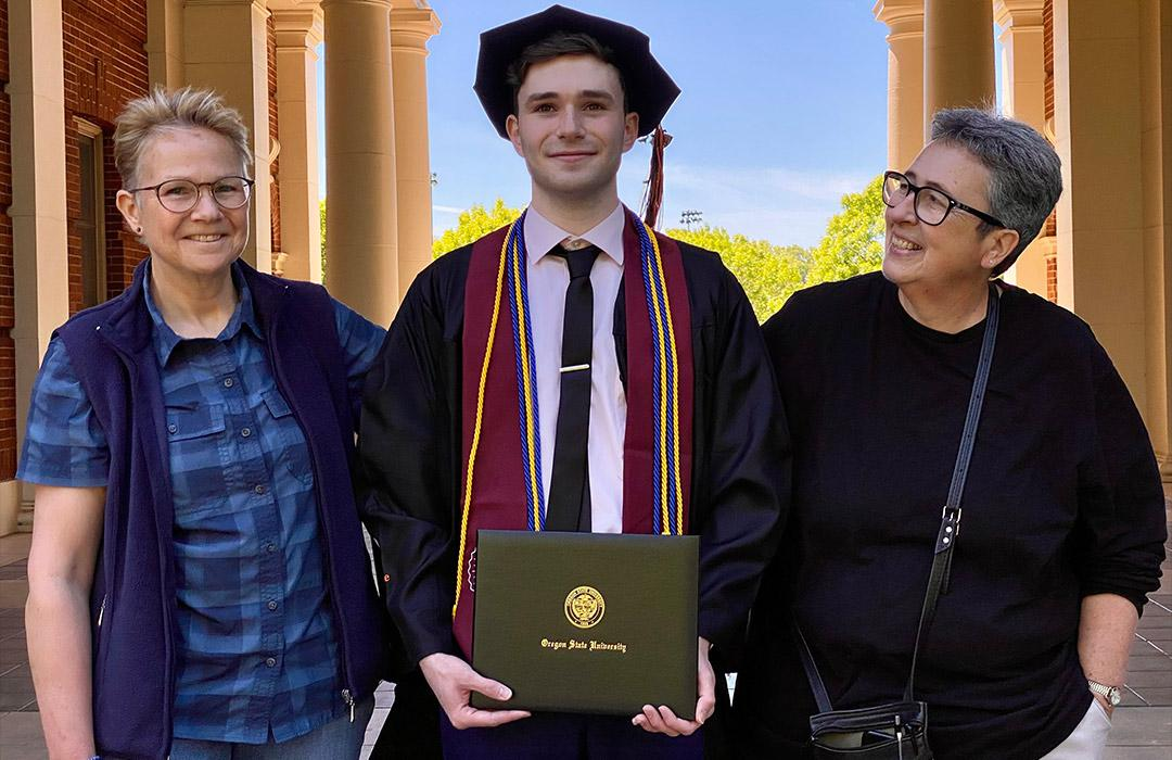 Young man in graduation gown with his two parents on either side smiling.