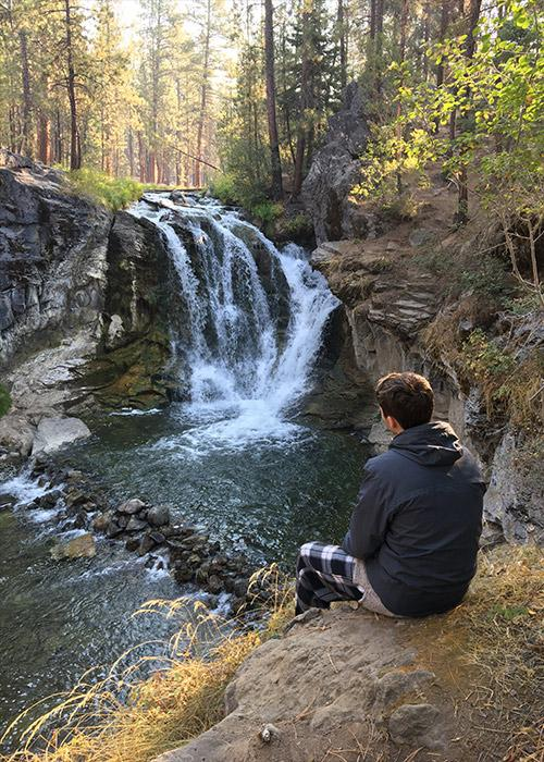 Young man looking at a waterfall in the distance.