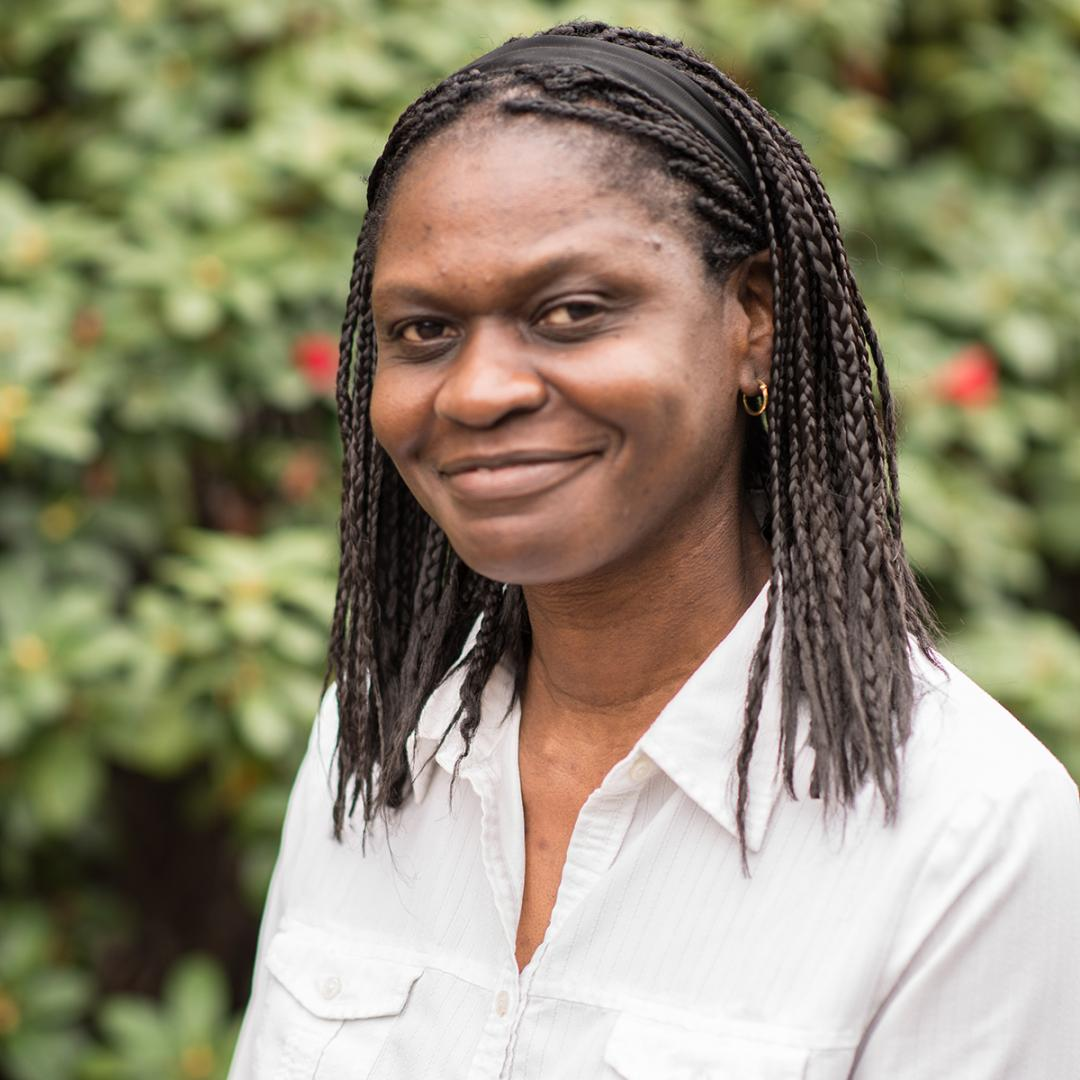 Headshot of Biochemist Afua Nyarko outdoors in front of green bushes