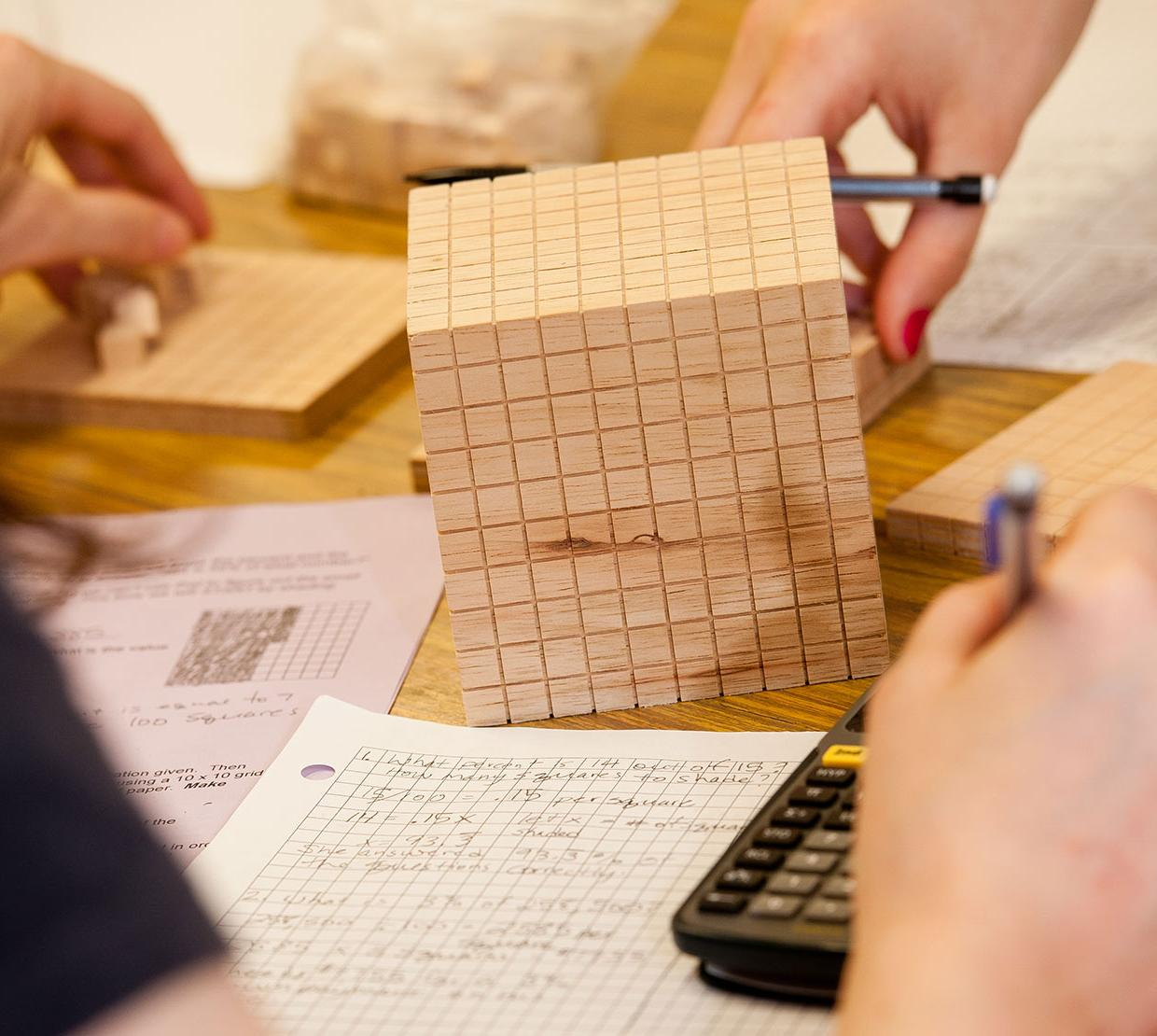 wooden cube on a table with math homework