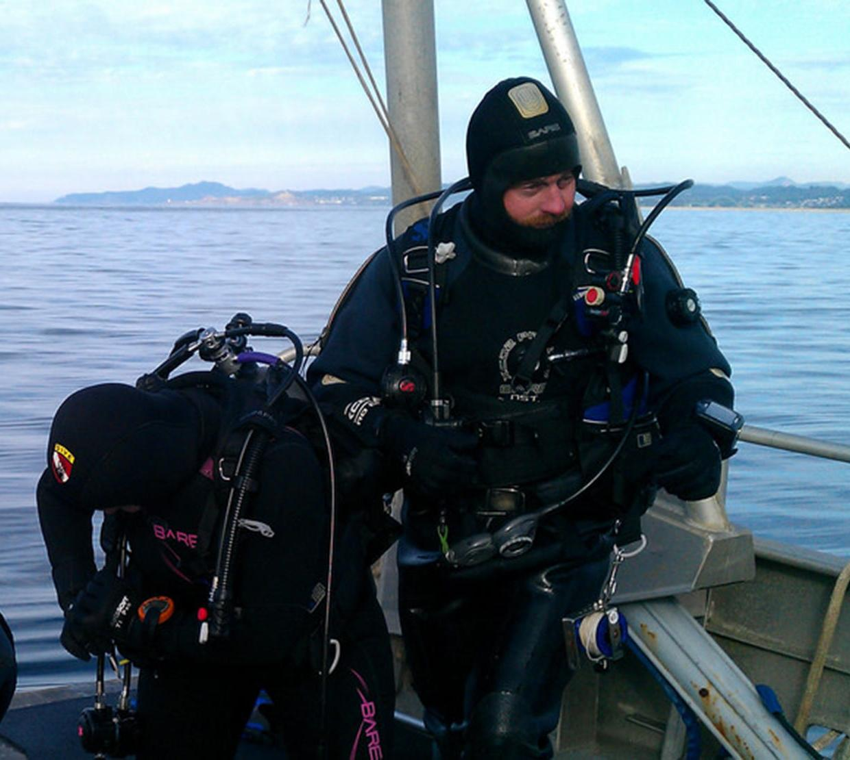 Scuba divers standing on edge of boat on sea