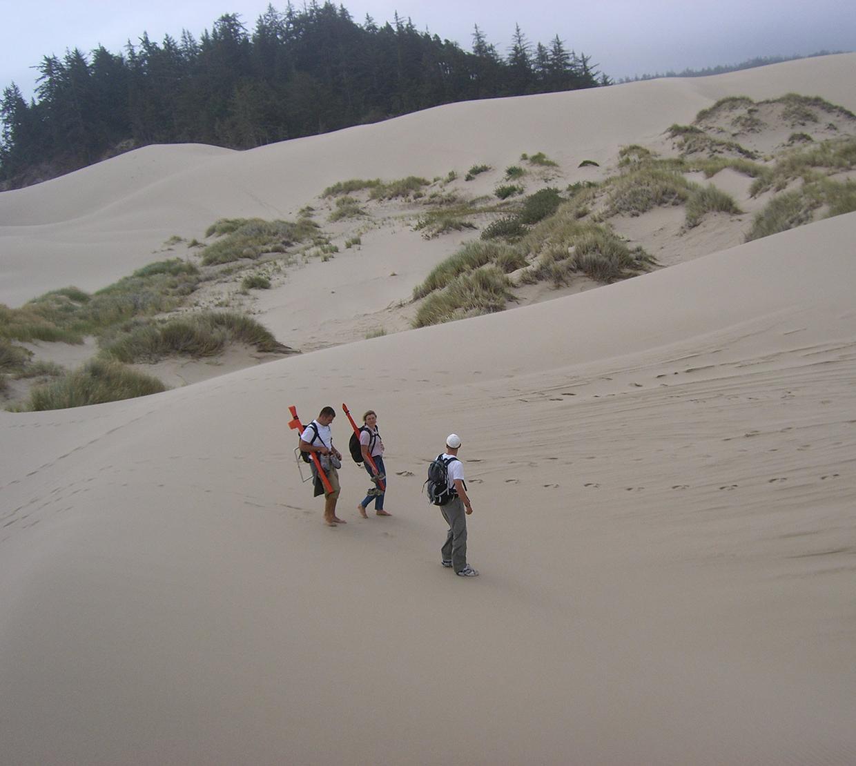 three people walking through Oregon sand dunes