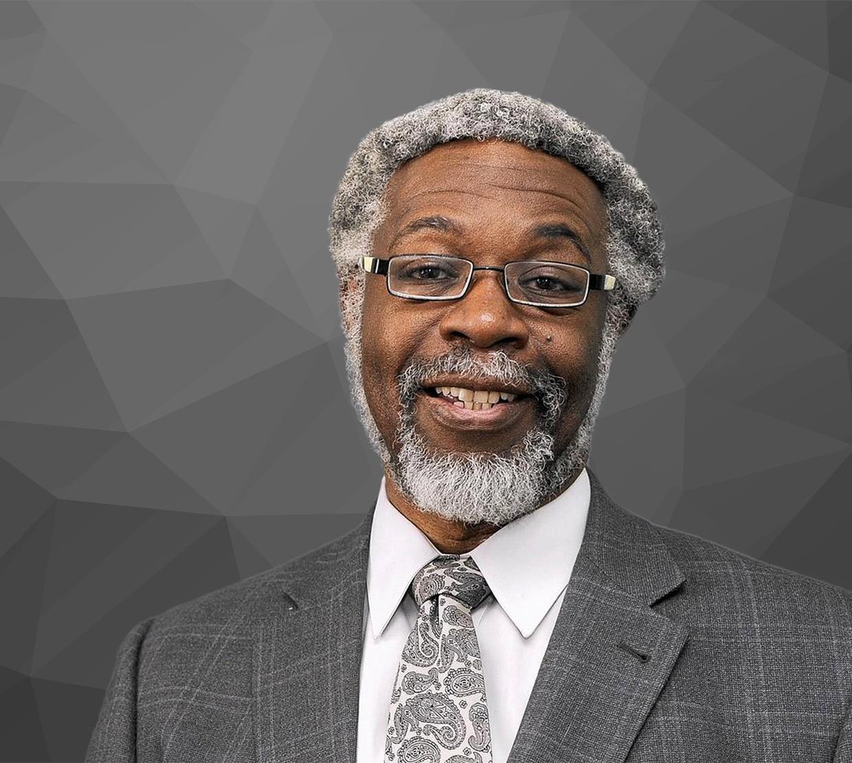 Sylvester James Gates Jr in front of grey geometric backdrop