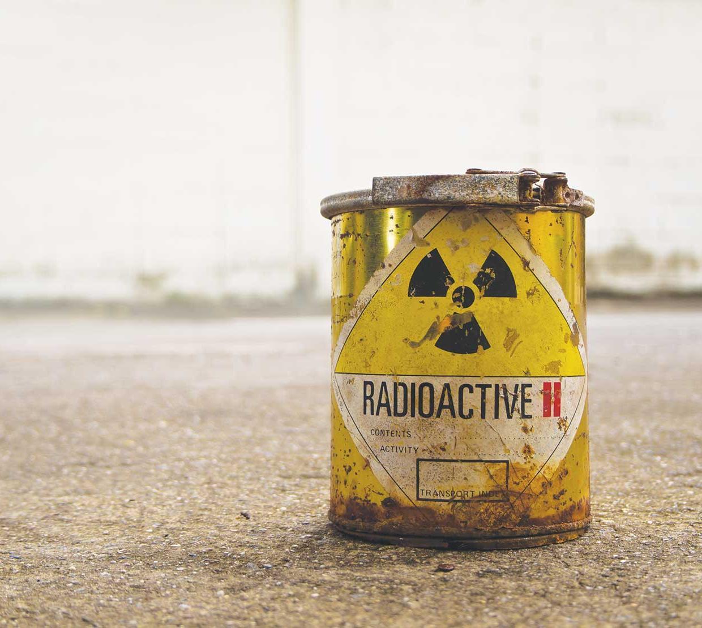 Radioactive waste bucket in concrete backdrop