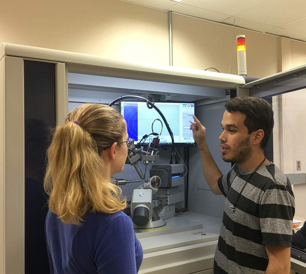male and female students looking over lab machinery