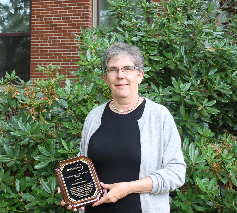 Heidi Schellman holding award in front of shrubbery