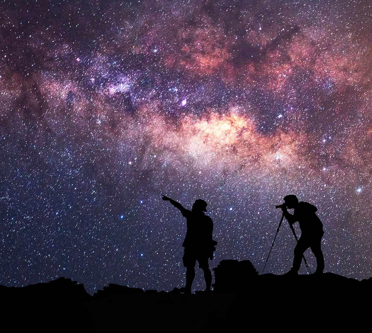 two silhouetted travelers gazing at stars