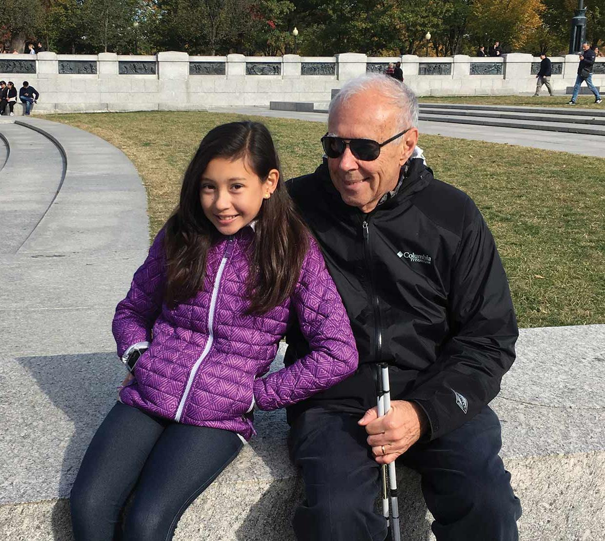 John Gardner with grand daughter sitting in a park