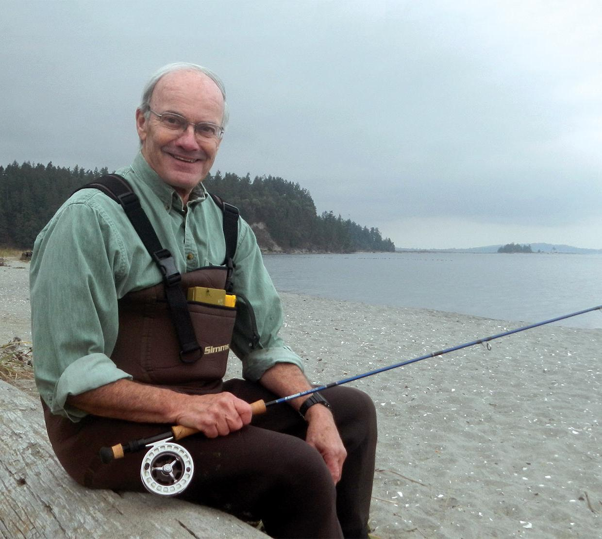James Winton holding fishing pole sitting on log in foggy beach