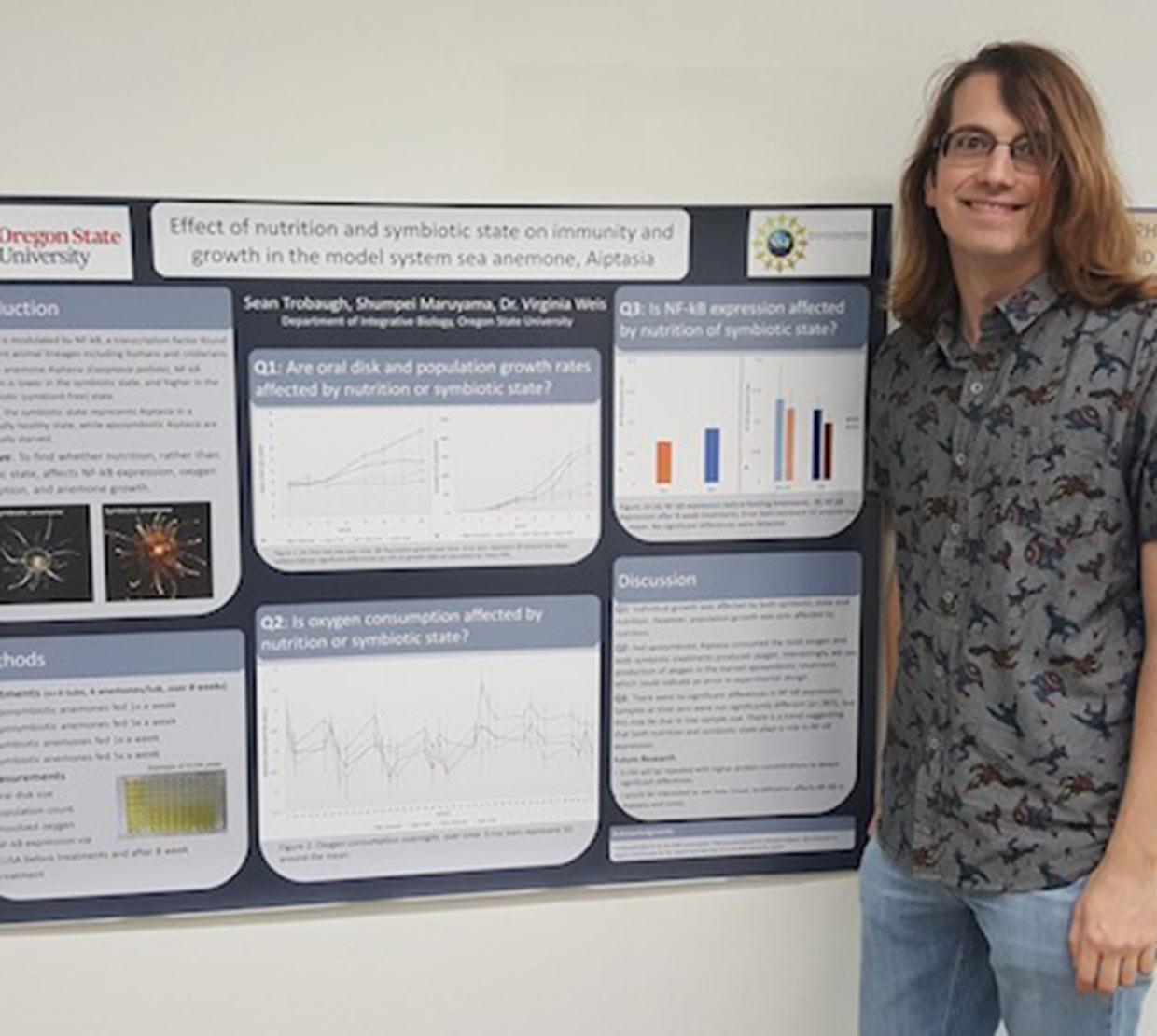 Sean Trobaugh in front of research poster