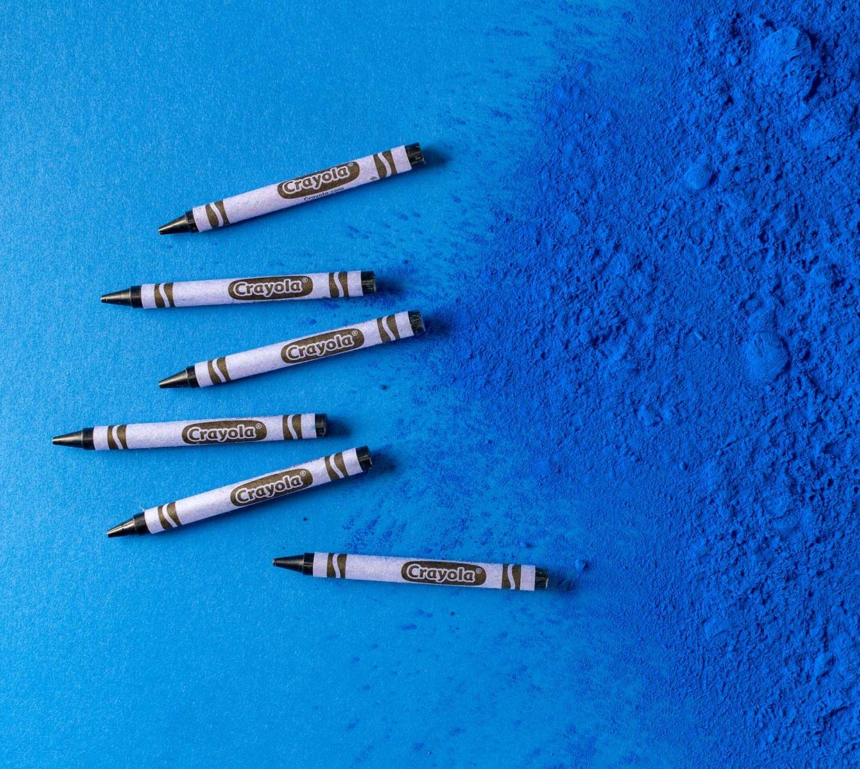 YInMn blue crayons on top of blue pigment texture