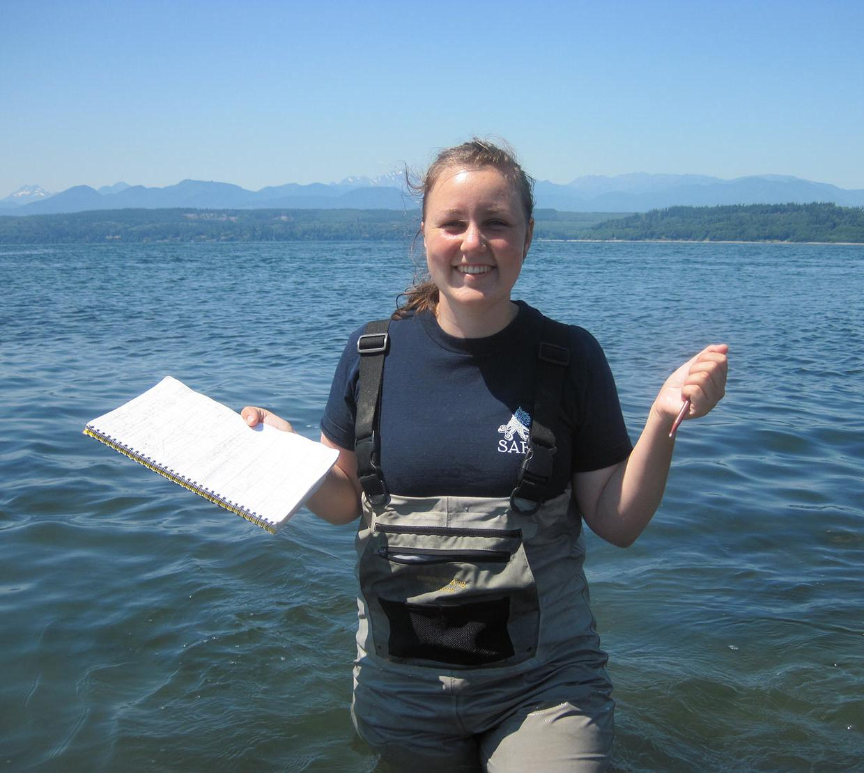 Shannon Hennessey standing in ocean with pen and paper