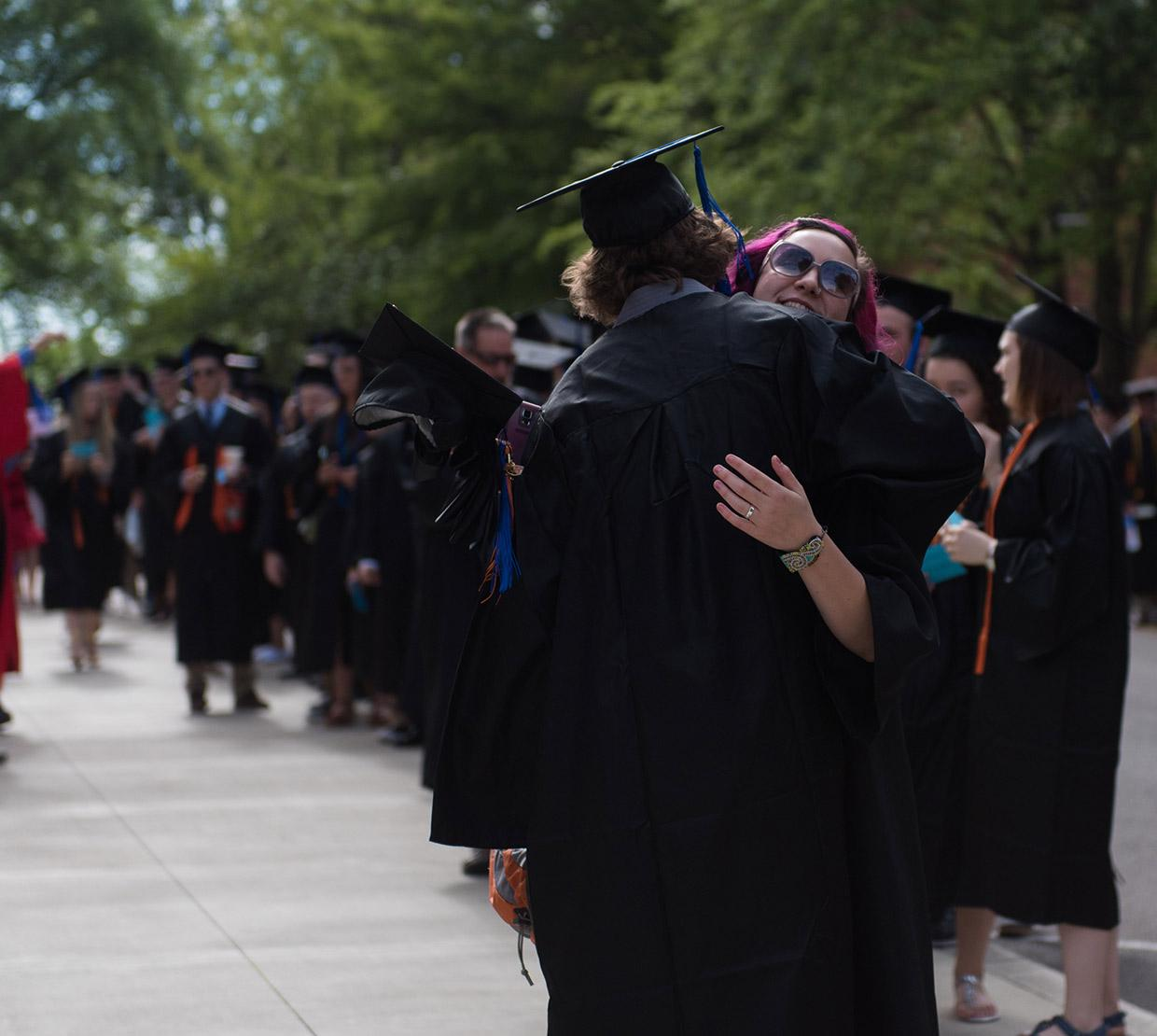 Two graduating students hugging each other in front of line of graduates in gowns