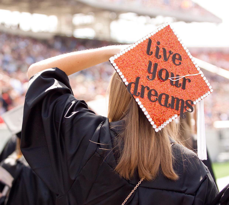 College graduate in decorated cap during graduation ceremony