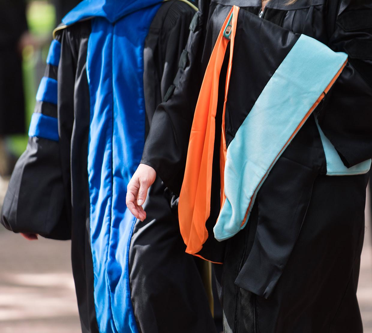 Two professors walking in doctoral gowns on campus