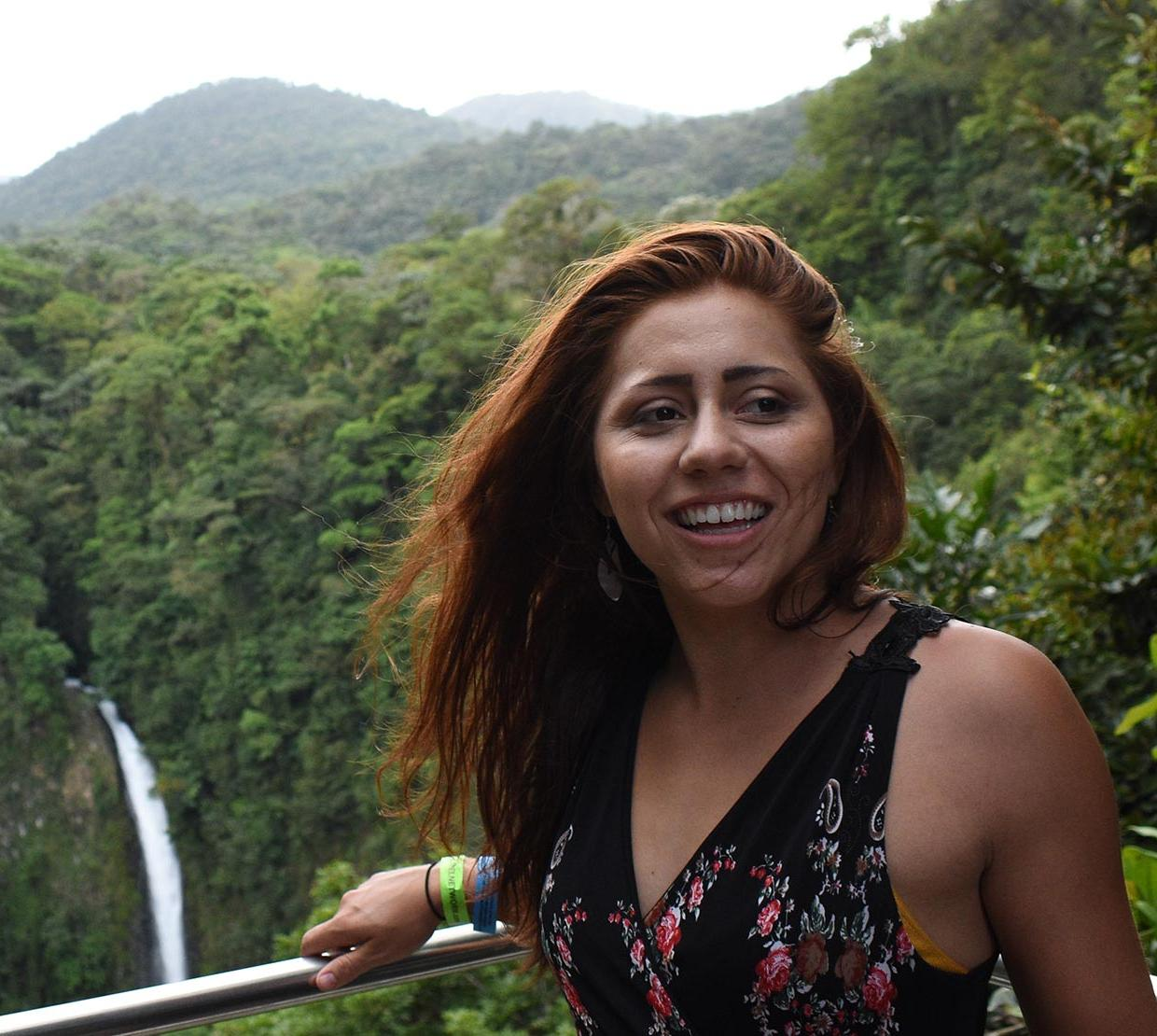 Tonya Allison standing in front of waterfall and forest