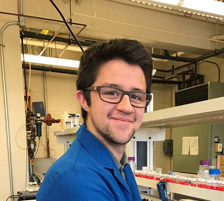 Collin Nicholas Muniz wearing a blue lab coat in chemistry lab