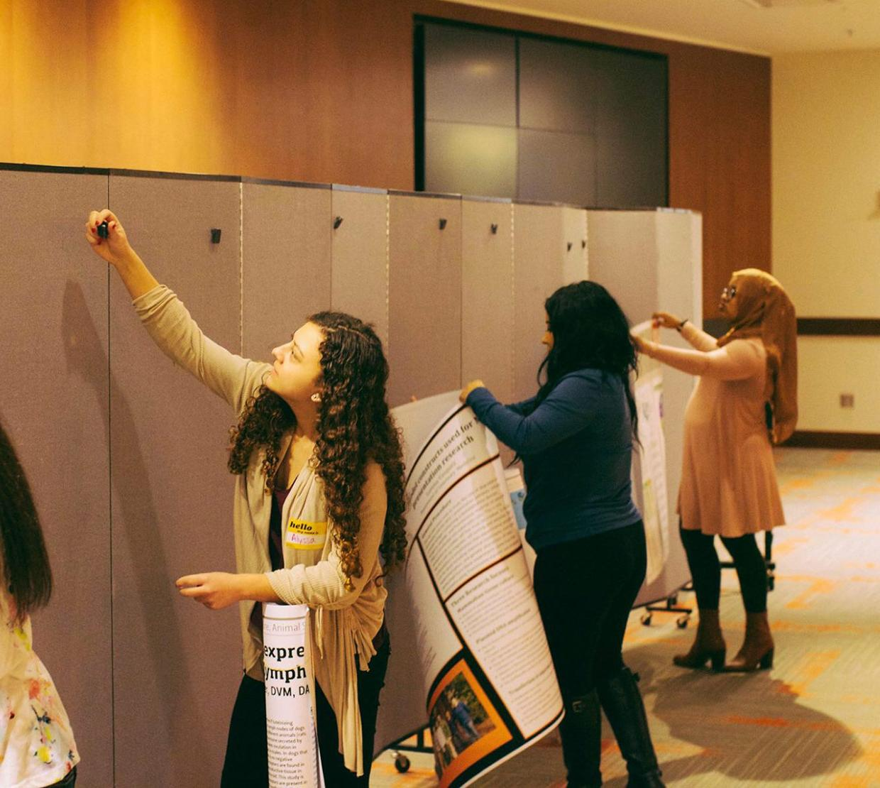 female STEM students setting up posters