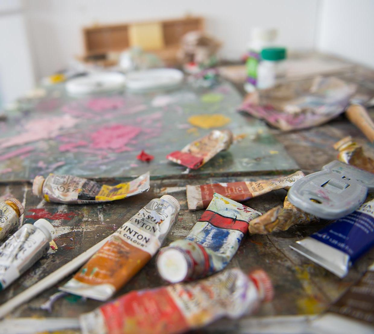paint tubes and palettes sitting on studio table
