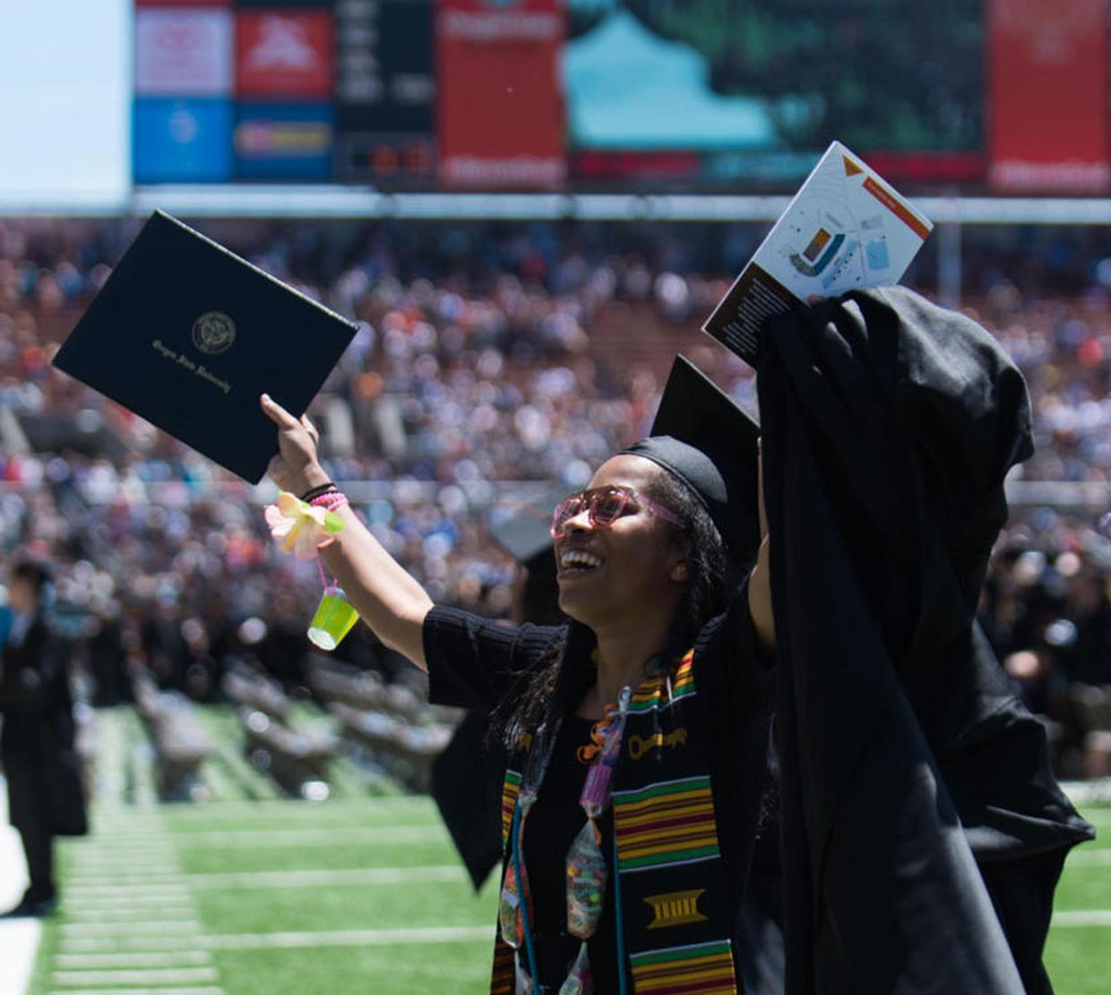 student holding up degree during graduation ceremony
