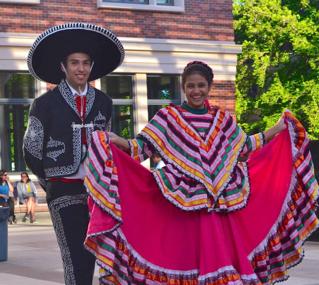 two students dressed in traditional Mexican festival garments in the SEC awning