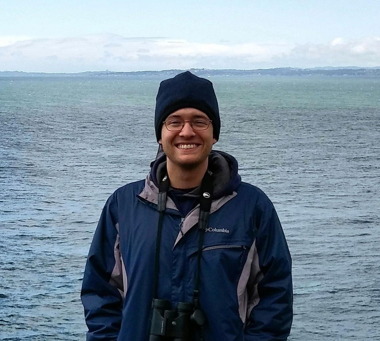 Zech Meunier standing in front of ocean