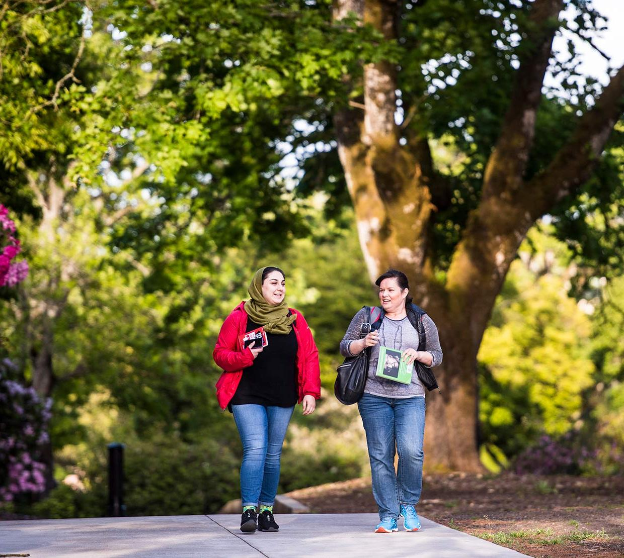 Two female students walking through campus in front of tree