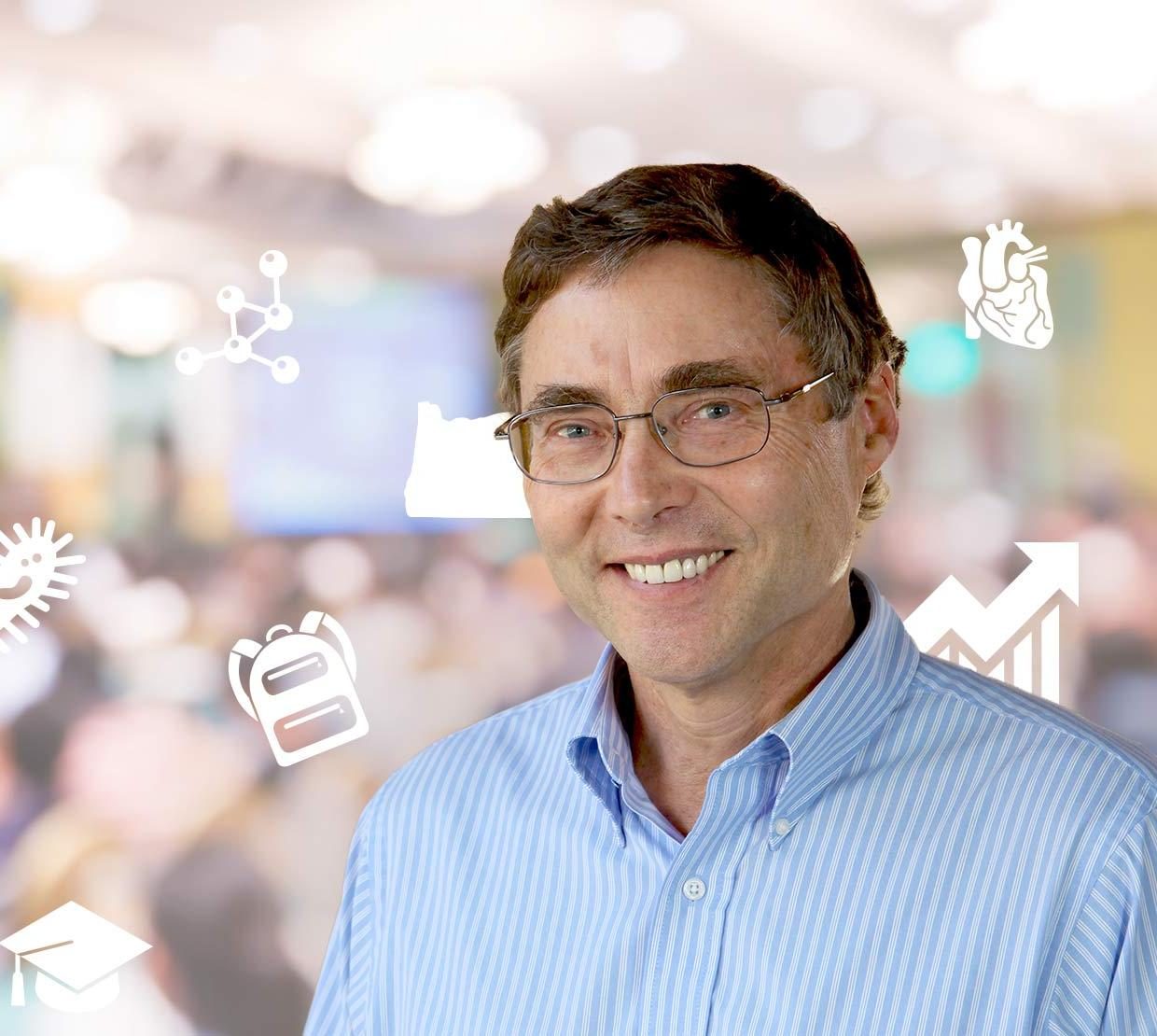 Carl Wieman in front of science major icons and audience